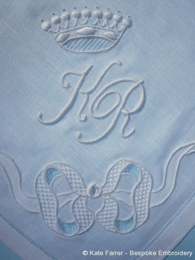 Fine whitework monogram in trailing stitch along with crown in drawn thread, trailing, eyelets, raised satin, padded satin, honeycomb stitch, whitework seeding